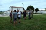 L'équipe de montage du chapiteau discute sur le terrain de foot